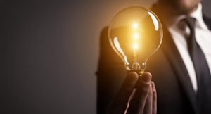 Man Holding Illuminated Lightbulb